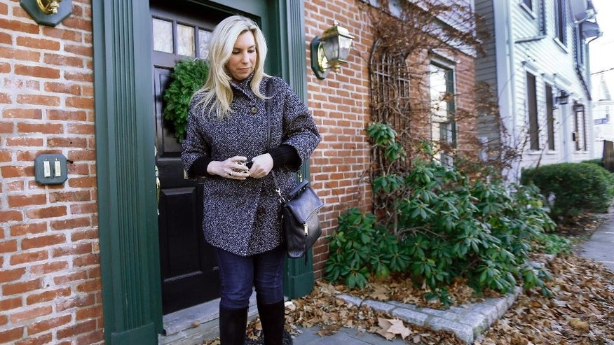 FILE - In this Dec. 12, 2014 file photo, Boston Marathon bombing survivor Heather Abbott walks out the door of her home in Newport, R.I. Rhode Island lawmakers are considering legislation to make victims of terrorist attacks eligible for compensation even if the attack happened outside the state. The bill is a response to the bureaucratic struggles encountered by Abbott when she applied for the state's crime victim compensation fund after the April 2013 attack. The House voted to pass the bill in March 2016. It faces a Senate committee hearing Tuesday, April 5, 2016 at the State House in Providence. (AP Photo/Elise Amendola, File)