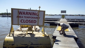 Larry Stanley, owner of Riverside Lake Marina, picks up tools from his dock Monday, April 4, 2016, after a warning sign was installed on one of his work boats at McKellar Lake. The City of Memphis has closed the boat ramp at 1875 McKellar Drive, which allows access to McKellar Lake, after a major sewer line transporting wastewater to the TE Maxson Wastewater Treatment Plant was damaged. State officials say the sewage leak has caused a major fish kill in McKellar Lake.  (Yalonda M. James/The Commercial Appeal)