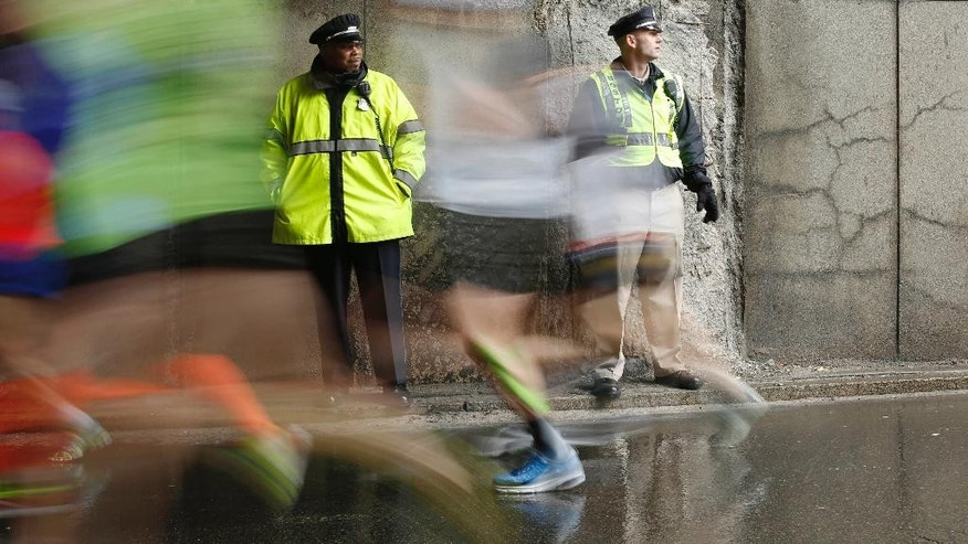 FILE - In this April 20, 2015 file photo, police officers stand watch as Boston Marathon participants race along the course in Boston. Multiple law enforcement agencies will provide security for the 120th Boston Marathon set to be run on Monday, April 18, 2016. (AP Photo/Robert F. Bukaty, File)