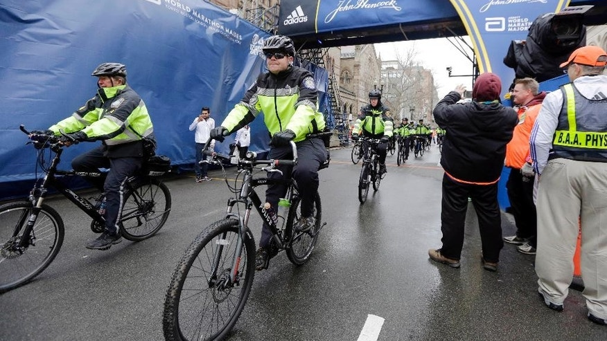 FILE - In this April 20, 2015 file photo, police officers patrol near the finish line of the Boston Marathon in Boston. Multiple law enforcement agencies will provide security for the 120th Boston Marathon set to be run on Monday, April 18, 2016. (AP Photo/Elise Amendola, File)