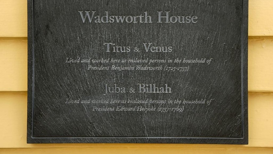 A newly unveiled plaque that honors four slaves that had been owned by and worked for Harvard's past presidents, is attached to Wadsworth House, on the campus of Harvard University, in Cambridge, Mass., Wednesday, April 6, 2016. (AP Photo/Steven Senne)