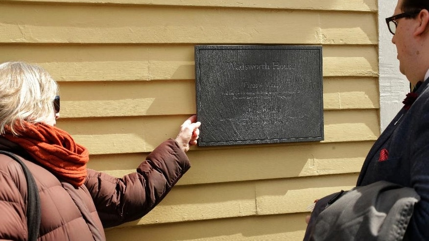Melissa Smith, of Cambridge, Mass., left, a Harvard Law School administrator, and Kyle Courtney, of Hanover, Mass., right, a copyright advisor at Harvard, examine a newly unveiled plaque, Wednesday, April 6, 2016, at Harvard's Wadsworth House, on the school's campus, in Cambridge, Mass. The plaque honors four slaves that had been owned by and worked for Harvard's past presidents. (AP Photo/Steven Senne)