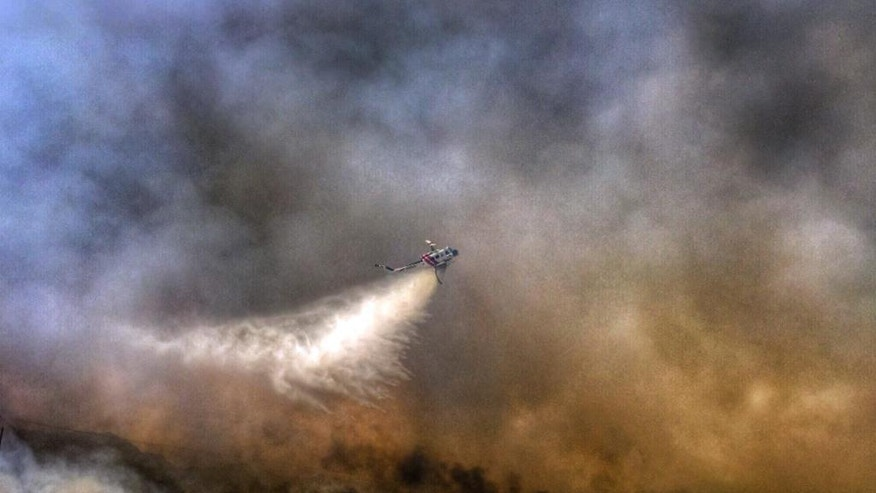 This photo provided by the San Bernardino County Fire Department shows a helicopter making a drop on a wildfire that started in western Arizona and jumped the Colorado River into California, near Needles, Calif., Wednesday, April 6, 2016. Two mobile home parks, Pirate's Cove and Park Moabi RV parks in the Mojave Desert south of Needles, were evacuated as firefighters on both sides of the river worked to surround the flames. (San Bernardino County Fire Department via AP) MANDATORY CREDIT