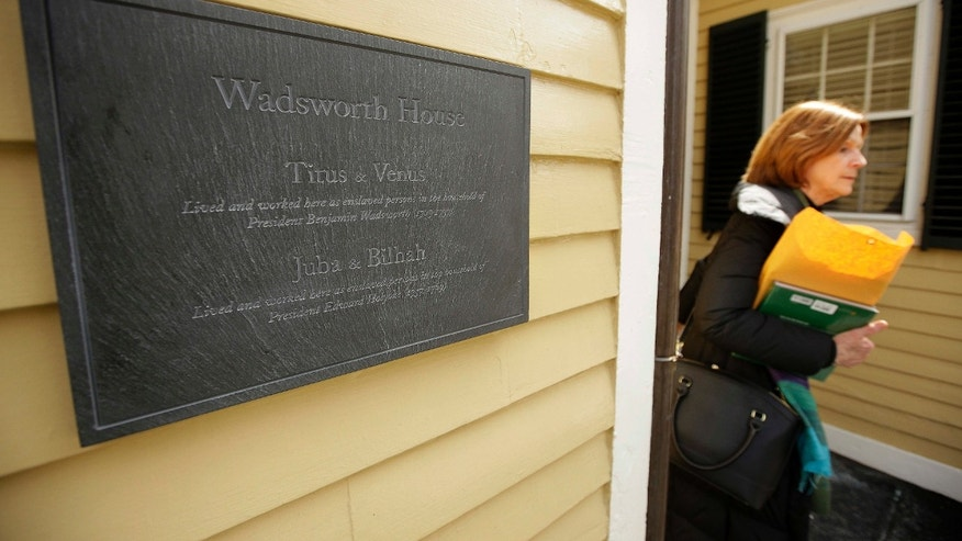 A passer-by walks near a newly unveiled plaque attached to Wadsworth House, Wednesday, April 6, 2016, on the campus of Harvard University that honors four slaves that had been owned by and worked for Harvard's past presidents, in Cambridge, Mass.