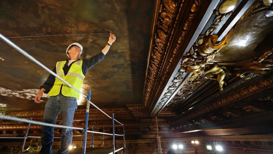 Mural director Bill Mensching helps prepare the ceiling for a new mural in the main catalog room at the New York Public Library in New York, Thursday, April 7, 2016. The library is installing a recreation of the century-old mural in its main catalog room. The original work was painted by the renowned American muralist and Tiffany Studios designer James Wall Finn. (AP Photo/Seth Wenig)