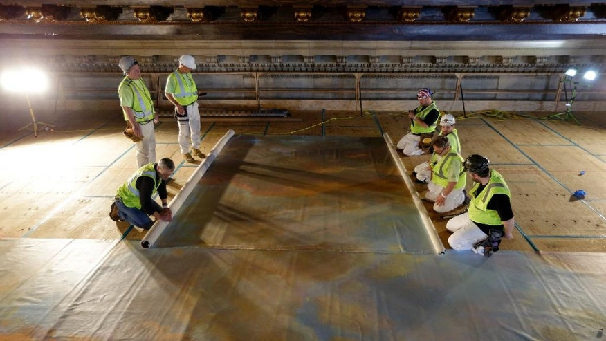 Workmen prepare to hang a large mural in two halves on a platform near the ceiling of the main catalog room at the New York Public Library in New York, Thursday, April 7, 2016. The library is installing a recreation of the century-old mural in its main catalog room. The original work was painted by the renowned American muralist and Tiffany Studios designer James Wall Finn. (AP Photo/Seth Wenig)