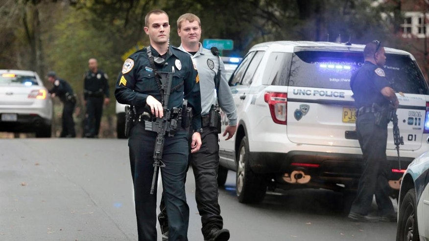 In this Dec. 2, 2015 photo, University of North Carolina at Chapel Hill police officers stand down and return to their patrol cars after answering a second man with a rifle call adjacent to the school's campus in Chapel Hill, N.C.  Federal data and Associated Press interviews and requests for records reveal that at least 100 college police agencies have added rifles over the past decade. (Harry Lynch/The News & Observer via AP) MANDATORY CREDIT