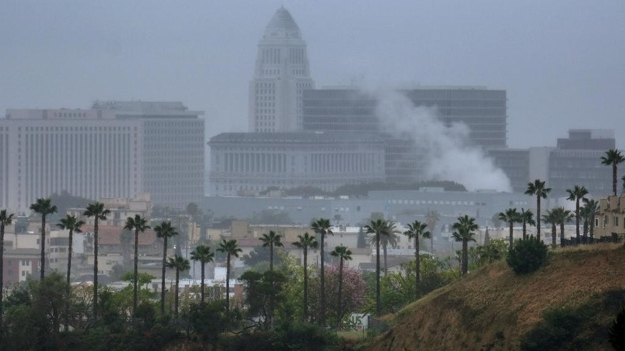 Los Angeles City Hall is seen through heavy clouds and rain in downtown on Friday, April 8, 2016. The first of two weather systems has brought showers to Southern California but rainfall has been scattered and mostly light. The National Weather Service says radar shows showers running across the region early Friday but not much of the rain is reaching the ground. (AP Photo/Richard Vogel)