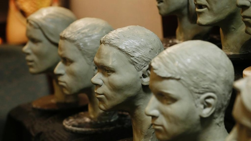Busts of unidentified crime victims are lined up in the offices of the Chief Medical Examiner for Virginia Tuesday, March 15, 2016, in Richmond, Va. The medical examiner's office is hoping a new set of facial sculptures created by the FBI will help identify eight people found dead in Virginia between 1972 and 2014. (AP Photo/Steve Helber)