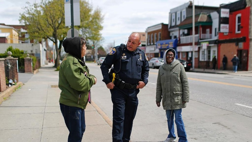 In this April 8, 2016 photo, Baltimore Police Department Officer Ken Hurst, center, chats with residents as he walks a foot patrol in Baltimore. Hurst is one of 450 police officers who are part of a foot patrol program aimed at getting officers out of their cars and onto the streets of the city's most dangerous neighborhoods, not to make arrests but to make friends. (AP Photo/Patrick Semansky)