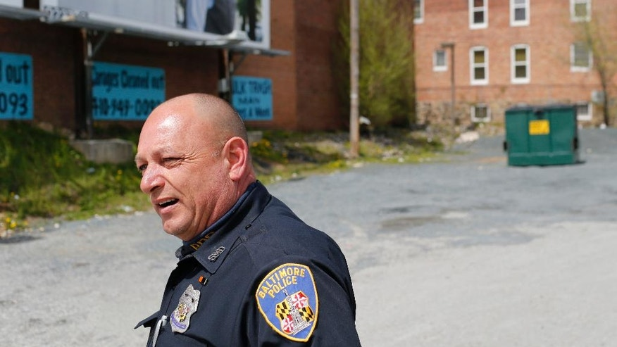 In this April 8, 2016 photo, Baltimore Police Department Officer Ken Hurst walks a foot patrol in Baltimore. For Hurst, policing is only one aspect of his job. He hands out flyers advertising jobs to those out of work. He's helping relocate a couple living in a dilapidated home, and he's working with locals to transform a vacant property into a community center.  (AP Photo/Patrick Semansky)