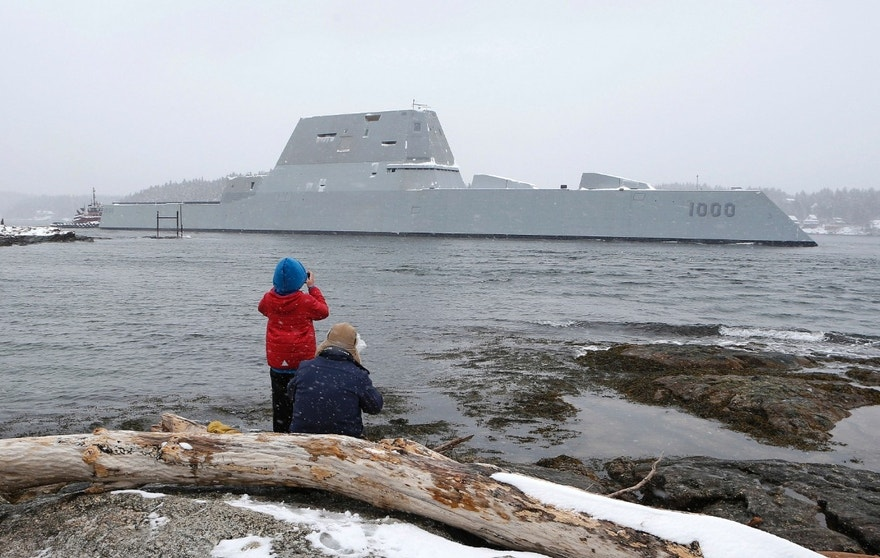 FILE - In this March 21, 2016 file photo, Dave Cleaveland and his son, Cody, photograph the USS Zumwalt as it passes Fort Popham at the mouth of the Kennebec River in Phippsburg, Maine, as it heads to sea for final builder trials. The ship is so stealthy that the U.S. Navy resorted to putting reflective material on its halyard  to make it visible to mariners during the trials. (AP Photo/Robert F. Bukaty, File)
