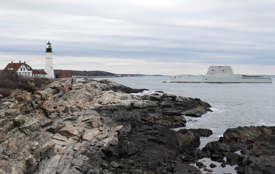 In this March 23, 2016 photo provided by Ben Davis, the USS Zumwalt passes Portland Headlight in Cape Elizabeth, Maine, during final builder trials. The 600-foot destroyer, due to be delivered to the Navy in April for acceptance trials, spent three days in the North Atlantic before returning to the shipyard late Thursday afternoon. (Ben Davis via AP) MANDATORY CREDIT