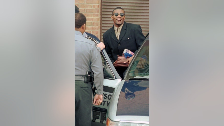 FILE- In this Feb. 19, 1996, file photo, Daniel Green laughs with deputies as he leaves the Robeson County Courthouse following the first day of defense testimony in Lumberton, N.C. Attorneys for Green, who was convicted of killing Michael Jordan's father, James Jordan, in 1993 and dumping his body in South Carolina, say they have new evidence to bolster their request for a new trial. (AP Photo/Karen Tam, File)