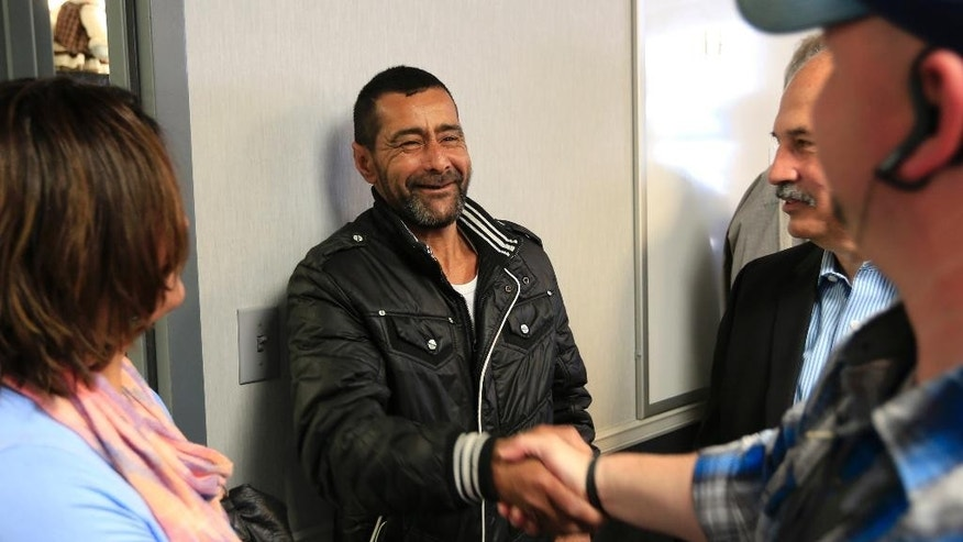 "Ahmad al-Abboud, center, shakes hands with a reporter following a news conference at Della Lamb Community Services in Kansas City, Mo., Monday, April 11, 2016. Ahmad al-Abboud and his family are the first Syrian family to be resettled in the U.S. under a speeded-up ""surge operation"" for refugees. (AP Photo/Orlin Wagner)"