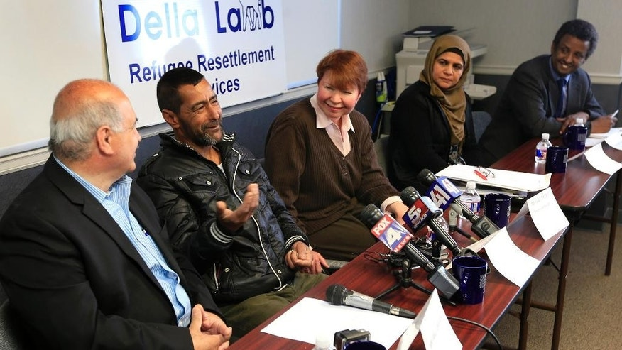 "Ahmad al-Abboud, second from left, speaks through an interpreter, Fariz Turkmani, left, during a news conference that included Judy Akers, center, Dr. Sofia Khan and Abdul Bakar, right, at Della Lamb Community Services in Kansas City, Mo., Monday, April 11, 2016. Ahmad al-Abboud and his family are the first Syrian family to be resettled in the U.S. under a speeded-up ""surge operation"" for refugees. (AP Photo/Orlin Wagner)"