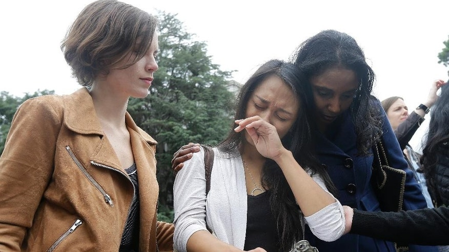 University of California graduate student Kathleen Gutierrez, center, is comforted by graduate student Erin Bennett, left, and Tyann Sorrell before all spoke at a news conference outside of Dwinelle Hall on the campus in Berkeley, Calif., Monday, April 11, 2016. Bennett and Gutierrez have filed a complaint regarding alleged sexual harassment by a University of California Berkeley professor. Sorrell has also made complaints against the same individual for sexual harassment. (AP Photo/Jeff Chiu)