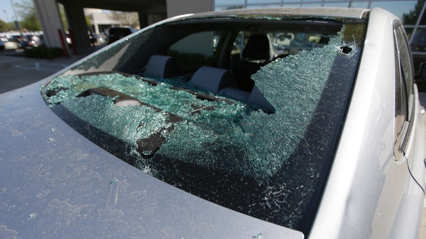 A car damaged by a hail storm sits in a parking lot in Plano, Texas.