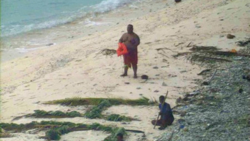 "This photo provided by U.S. Navy released Thursday, April 7, 2016, shows a man waving a life jacket and two others looking on as a U.S. Navy P-8A maritime surveillance aircraft discovers them on the uninhabited island of Fanadik. The three men were back to safety on Thursday, three days after going missing. Officials say three men who had been missing for three days were rescued from a deserted Pacific island after a U.S. Navy plane spotted a gigantic ""help"" spelled out with palm leaves. (Ensign John Knight/U.S. Navy via AP)"