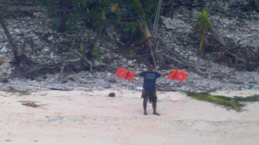 "This photo provided by U.S. Navy released Thursday, April 7, 2016, shows a man waving a life jacket as a U.S. Navy P-8A maritime surveillance aircraft discovers them on the uninhabited island of Fanadik. The three men were back to safety on Thursday, three days after going missing. Officials say three men who had been missing for three days were rescued from a deserted Pacific island after a U.S. Navy plane spotted a gigantic ""help"" spelled out with palm leaves. (Ensign John Knight/U.S. Navy via AP)"