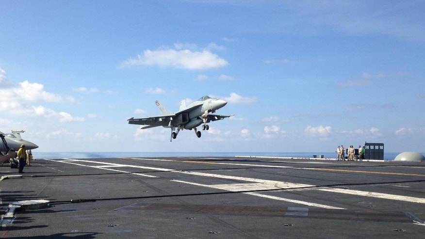 An FA-18 jet fighter takes off on the USS John C. Stennis, aircraft carrier in the South China Sea on Friday, April 15, 2016.  U.S. Defense Secretary Ash Carter visited the aircraft carrier during a trip to the region.  (AP Photo/Lolita C. Baldor)