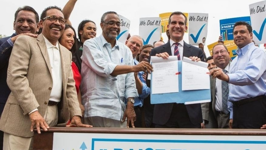 June 13, 2015: Los Angeles Mayor Eric Garcetti, center right, joins members of the City Council and community leaders in a photo after he signed into law an ordinance that will gradually raise the minimum wage to $15 an hour by 2020 in Los Angeles.