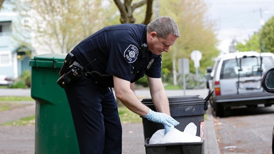 Seattle Police officer Aaron Stoltz searches garbage and recycling bins, Friday, April 15, 2016, after human remains were found in a nearby container in Seattle. Seattle Assistant Police Chief Robert Merner said authorities were investigating the probable connection between the remains found Friday and the recent murder of Ingrid Lyne, whose partial remains were found in a recycling bin earlier in the week. (AP Photo/Ted S. Warren)