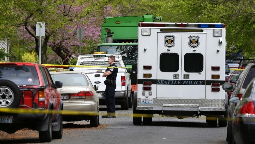 A Seattle Police officer stands near a garbage truck and ambulance, Friday, April 15, 2016, where human remains were found in Seattle. Seattle Assistant Police Chief Robert Merner said authorities were investigating the probable connection between the remains found Friday and the recent murder of Ingrid Lyne, whose partial remains were found in a recycling bin earlier in the week. (AP Photo/Ted S. Warren)