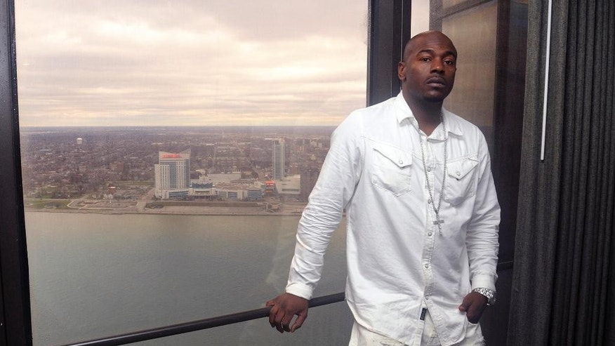 In a photo from March 28, 2016, Robert Wilcoxson stands at his hotel window in Detroit, with a view of the city of Windsor, Ontario behind him. Wilcoxson is one of two people freed by the North Carolina Innocence Inquiry Commission, and he received $5 million in compensation. (AP Photo/Jose Juarez)