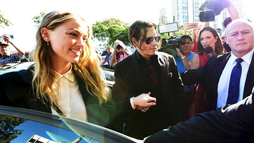 Johnny Depp, center, and wife Amber Heard, left, arrive at the Southport Magistrates Court on the Gold Coast, Australia, Monday, April 18, 2016. Heard pleaded guilty to providing a false immigration document amid allegations she smuggled the couple's dogs into Australia. (Dave Hunt/AAP Image via AP) NO ARCHIVING, AUSTRALIA OUT, NEW ZEALAND OUT, PAPUA NEW GUINEA OUT, SOUTH PACIFIC OUT