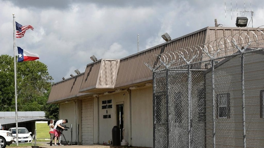 File - In this July 22, 2015, file photo, news media work outside the Waller County Jail, in Hempstead, Texas. Several recommendations issued by a panel investigating the small-town Texas jail where Sandra Bland died could be difficult to implement, including a call to separate sheriff and jail operations that may run afoul of state law.  (AP Photo/Pat Sullivan, File)