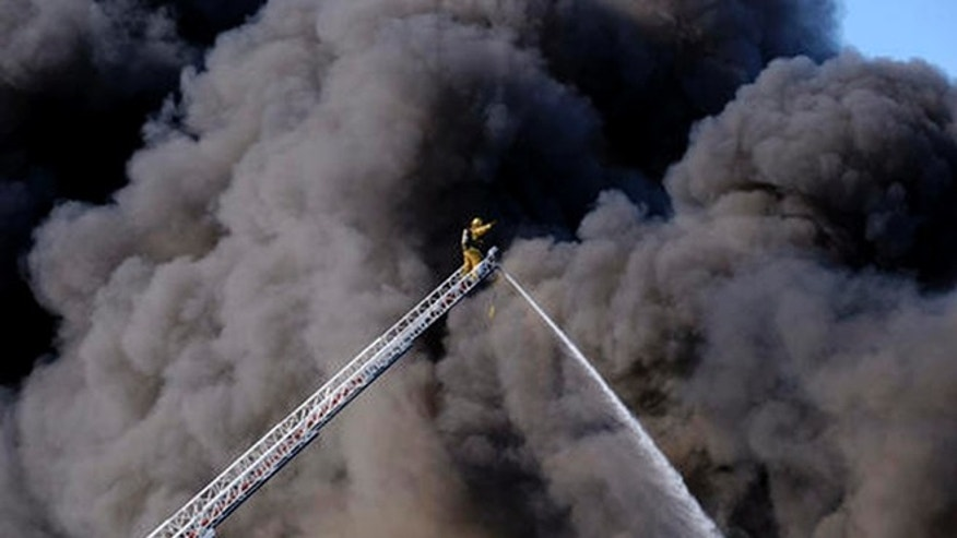 A firefighter responds to a fire at an auto wrecking yard in the Sun Valley section of Los Angeles in the San Fernando Valley as a huge plume of thick, black smoke rises over them on Sunday, April 17, 2016. (AP)