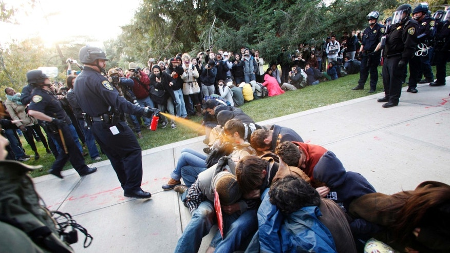 Nov. 18, 2011: University of California, Davis Police Lt. John Pike uses pepper spray to move Occupy UC Davis protesters while blocking their exit from the school's quad in Davis, Calif.