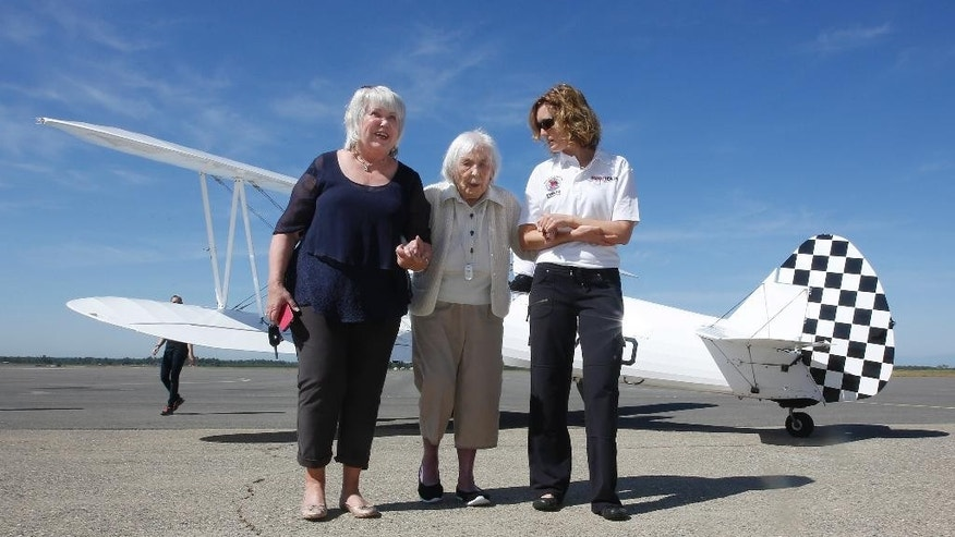Lynn Balmer, 108, center, the oldest living female military veteran, is escorted across the tarmac by Lyn Dorenzo, left, and Merilyn Chaffee, right, after viewing a World War II-era biplane at the Chico Air Museum, Monday, April 18, 2016, in Chico, Calif. Balmer was scheduled to take a flight aboard the aircraft, but decided against it in the morning, said Darryl Fisher, president of the Ageless Aviation Dreams Foundation, a group that gets aging veterans into the sky. (AP Photo/Rich Pedroncelli)