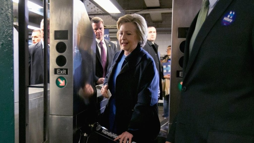 "FILE - In this April 7, 2016 file photo, Democratic presidential candidate Hillary Clinton holds her Metrocard as she goes through the turnstile to enter the subway in the Bronx borough of New York. Clinton, Bernie Sanders and Donald Trump are all boasting about their New York City credentials. But who really makes the cut as  a local legend? We put the candidates to the test with a ""New Yorker Scorecard.""  (AP Photo/Richard Drew, File)"