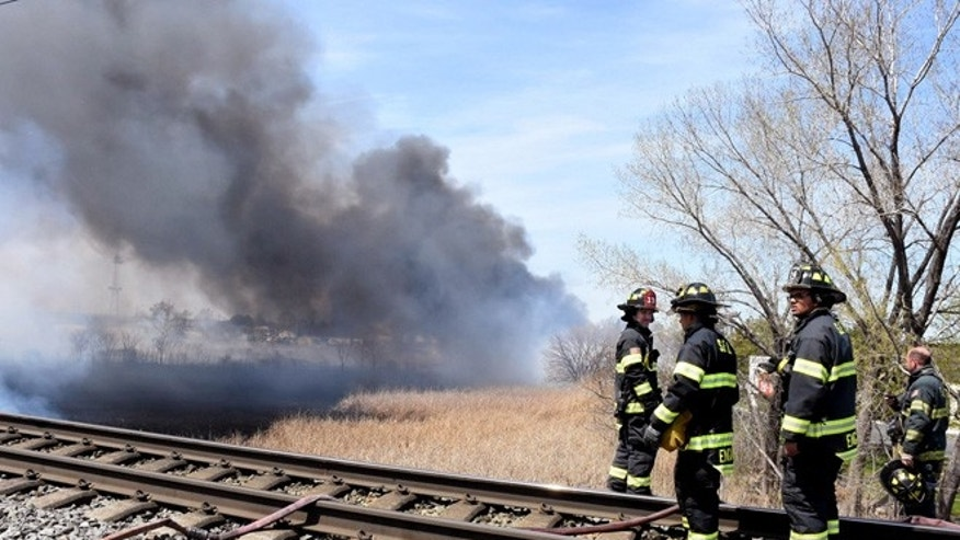 April 19, 2016: Firefighters battle a brush fire in in Secaucus, N.J. (Joe Shine/The Jersey Journal via AP) MANDATORY CREDIT