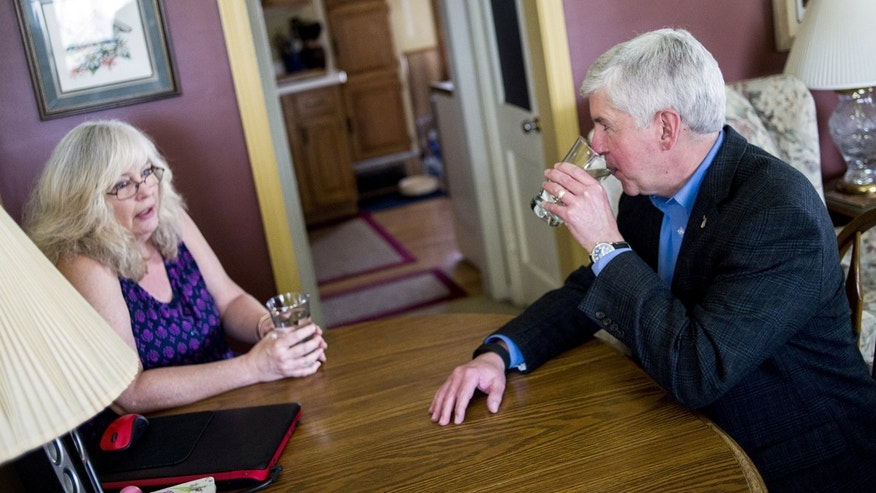 April 18, 2016: Michigan Gov. Rick Snyder, right, drinks filtered Flint, Mich., tap water with Flint resident Cheryl Hill while listening to her concerns with the city's ongoing water crisis at her home.