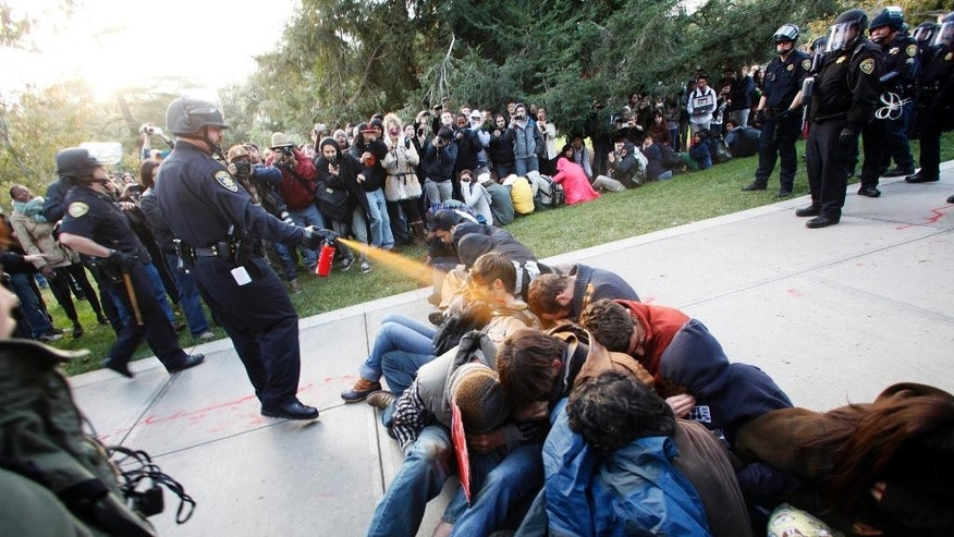 FILE - In this Nov. 18, 2011 file photo, University of California, Davis Police Lt. John Pike uses pepper spray to move Occupy UC Davis protesters while blocking their exit from the school's quad in Davis, Calif. Some California lawmakers want the head of the University of California, Davis to quit over the school's public relations spending after students were pepper-sprayed. As of Thursday, April 15, 2016, at least seven state lawmakers are calling for the resignation of school Chancellor Linda Katehi. The demands follow reports by the newspaper that the school paid image consultants at least $175,000 to try to clean up the online image of the university and Katehi after the 2011 incident. (Wayne Tilcock/The Enterprise via AP, File)