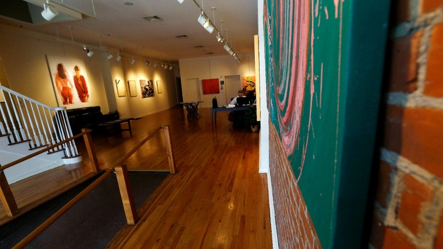 Artwork, left, by painter Tom Dash, depicting a partially a nude woman, hangs at Borghi Fine Art Gallery Tuesday.