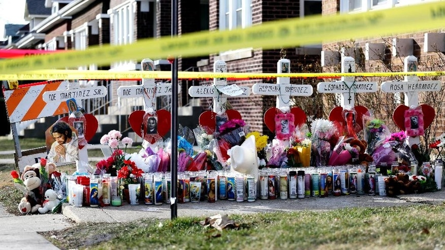 FILE - In this Feb. 7, 2016 file photo, crosses and crime scene tape are seen outside a home in Chicago where six bodies, four adult and two children, were found Feb. 4. A new report by the Cook County medical examiner on Tuesday, April 19, 2016, reveals details of the autopsies of three of the victims. Autopsies for the other three victims were previously released. (AP Photo/Nam Y. Huh, File)