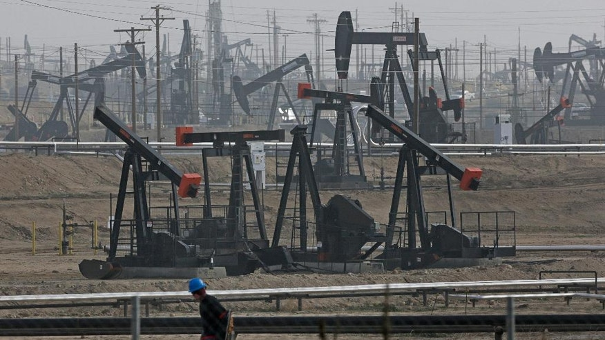 FILE - In this Jan. 16, 2015, file photo, a person walks past pump jacks operating at the Kern River Oil Field in Bakersfield, Calif. California regulators on Monday expanded their list of thousands of state-permitted oil and gas wells where below-ground injections may be contaminating drinking-water reserves. Californians breathe some of the nation's dirtiest air, according to a report card issued Wednesday, April 20, 2016, that gives failing grades to communities in the Central Valley's farming region and Los Angeles area. (AP Photo/Jae C. Hong, File)