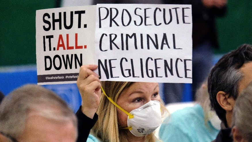 FILE - In this Saturday, Jan. 16, 2016, file photo, Porter Ranch resident Tera Lecuona holds a protest sign over a gas leak at the Southern California Gas Company's Aliso Canyon Storage Facility during a hearing in the Granada Hills section of Los Angeles. Californians breathe some of the nation's dirtiest air, according to a report card issued Wednesday, April 20, 2016, that gives failing grades to communities in the Central Valley's farming region and Los Angeles area. (AP Photo/Richard Vogel, File)