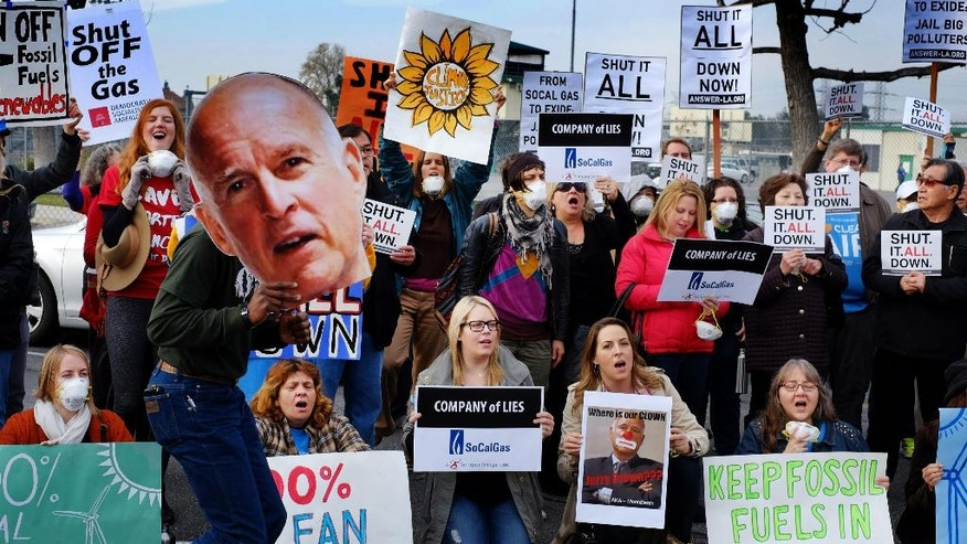 FILE - In this Jan. 16, 2016, file photo, protestors carry a photo of Gov. Jerry Brown and demand a shut down of the Southern California Gas Company's Aliso Canyon Storage Facility near Porter Ranch in Los Angeles. Californians breathe some of the nation's dirtiest air, according to a report card issued Wednesday, April 20, 2016, that gives failing grades to communities in the Central Valley's farming region and Los Angeles area. (AP Photo/Richard Vogel, File)