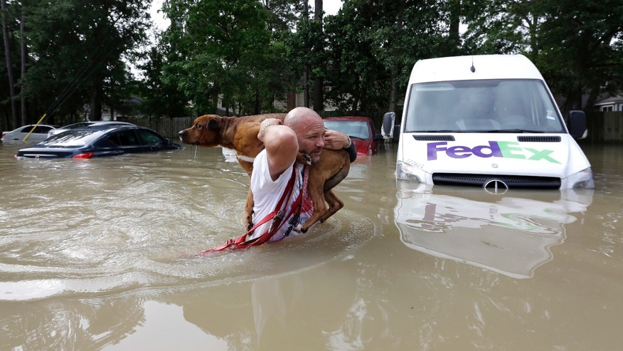 Louis Marquez carries his dog, Dallas, through floodwaters after rescuing the dog from his flooded apartment Tuesday in Houston.
