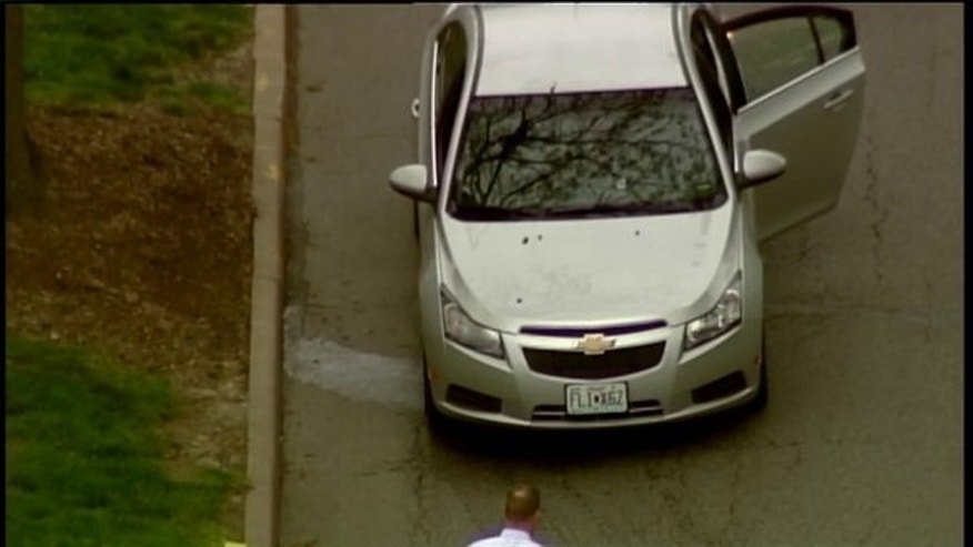Police investigating a car with apparent bullet holes on campus.