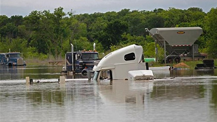 Trucks at a repair shop in Texas Highway 114 are flooded as Lake Bridgeport continues to rise with runoff from recent rains, in Bridgeport, Texas, Wednesday, April 20, 2016. The death toll has reached several in Southeast Texas flooding after storms dumped more than a foot of rain. (Rodger Mallison/Star-Telegram via AP) MANDATORY CREDIT