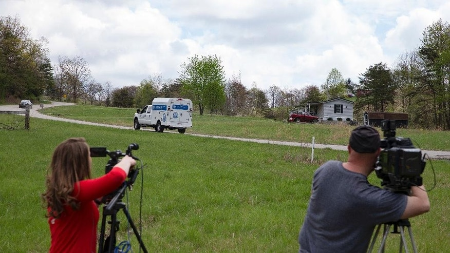 Media personnel video crime scene investigation vehicles as they drive towards the location of a reported multiple shooting, Friday, April 22, 2016, in Pike County, Ohio. Shootings with multiple fatalities were reported along a road in rural Ohio on Friday morning, but details on the number of deaths and the whereabouts of the suspect or suspects weren't immediately clear. The attorney general's office said a dozen Bureau of Criminal Investigation agents had been called to Pike County, an economically struggling area in the Appalachian region some 80 miles east of Cincinnati. (AP Photo/John Minchillo)