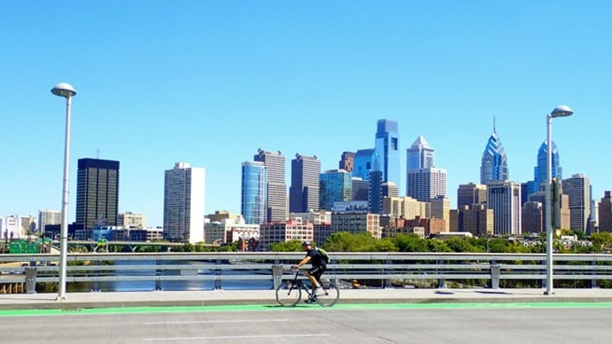 Philadelphia, PA, USA – August 28, 2014: Bicyclist on the South Street Bridge with the Philadelphia Skyline behind him.