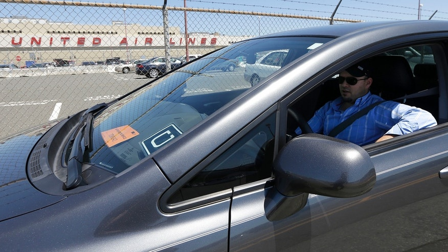 July 15, 2015: Uber driver Karim Amrani sits in his car parked near the San Francisco International Airport parking area in San Francisco.
