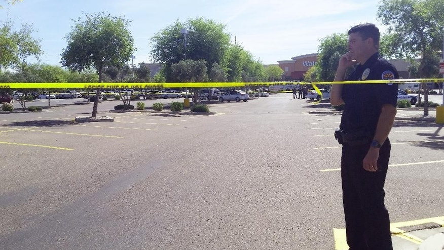 Chandler police spokesman Seth Tyler stands behind crime tape at the scene of a police involved shooting at a Walmart store on Saturday, April 23, 2016 in Chandler, Ariz. Authorities in a Phoenix suburb say two officers have been shot and a suspect is dead. Tyler says both officers are hospitalized in stable condition. (AP Photo/Terry Tang)